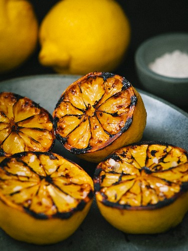 Grilled lemons with carmelized and burnt edges in a shallow stone bowl with sea salt crystals