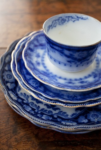 A stack of blue and white plates with a cup on top