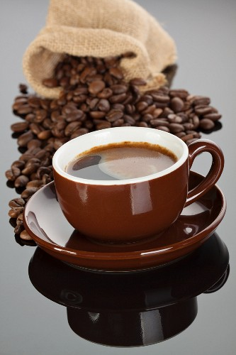 An espresso in a brown cup in front of a sack of coffee beans
