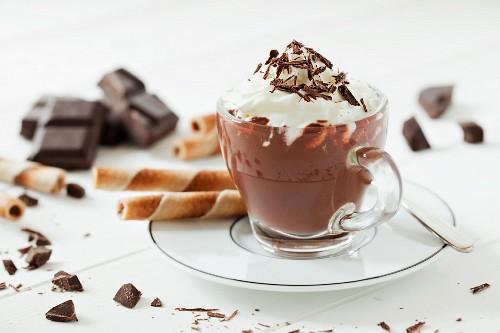 Eine Tasse heiße Schokolade mit Sahne und Schokoladenraspeln, Schokoladenstücke und Waffelröllchen