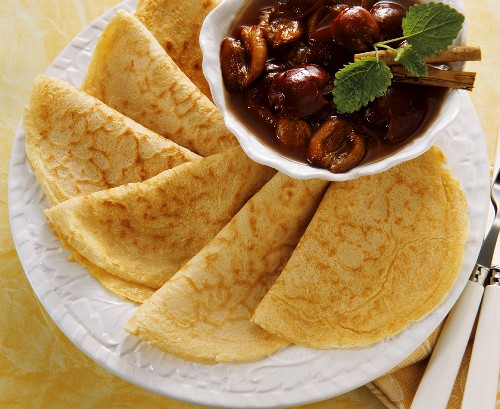 Several folded crepes with a bowl of cherries