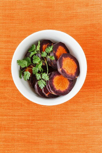 Slices of purple carrots in a white bowl with coriander leaves