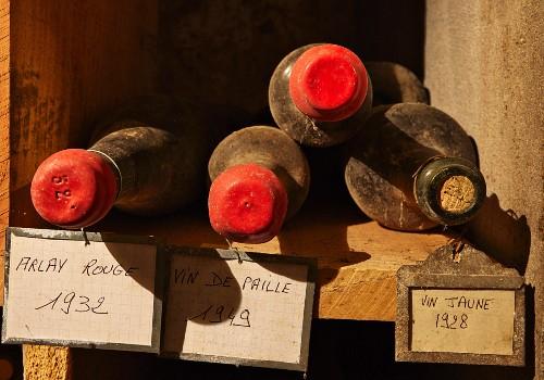 Vier staubige Weinflaschen in rustikalem Holzregal
