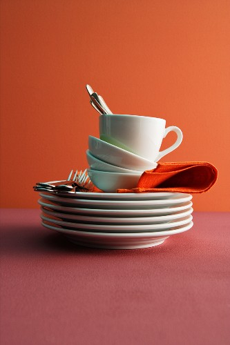 A stack of plates, bowls and a cup