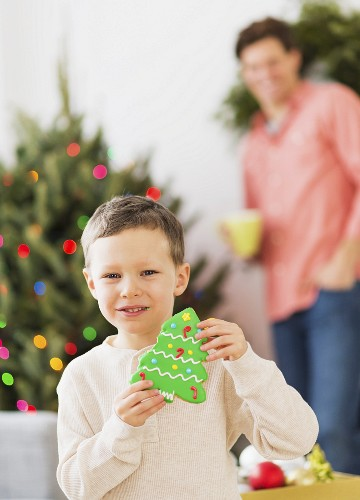 A boy holding a Christmas tree-shaped biscuit