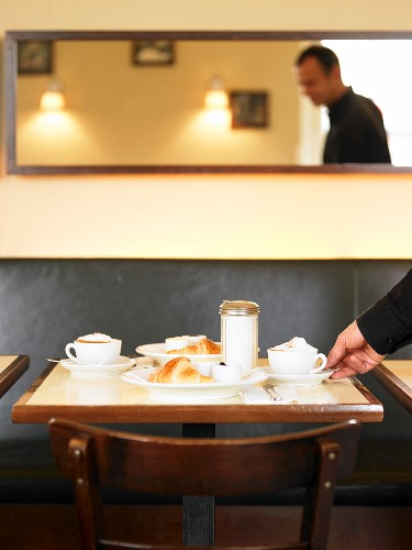 A table laid for breakfast with cappuccino and croissants in a bistro cafe
