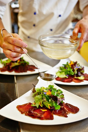 A chef drizzling dressing onto a salad