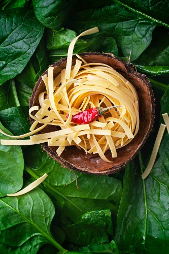 Tagliatelle and a chilli pepper in a coconut shell on a bed of spinach leaves