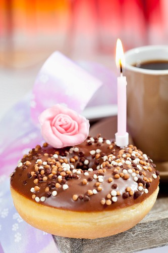 A doughnut with chocolate icing and a birthday candle