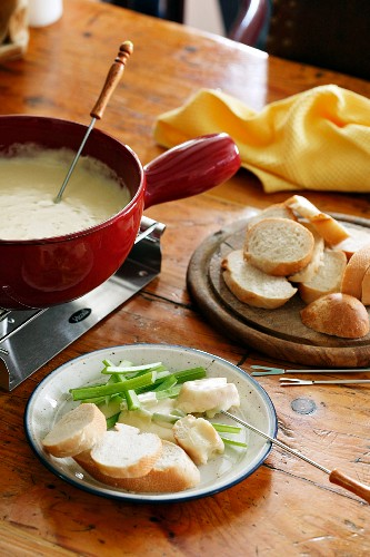 Cheese fondue with spring onions and a baguette