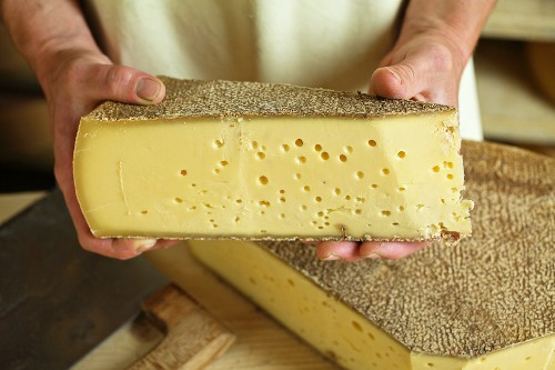 A dairyman presenting a slice of Vorarlberg Mountain Cheese