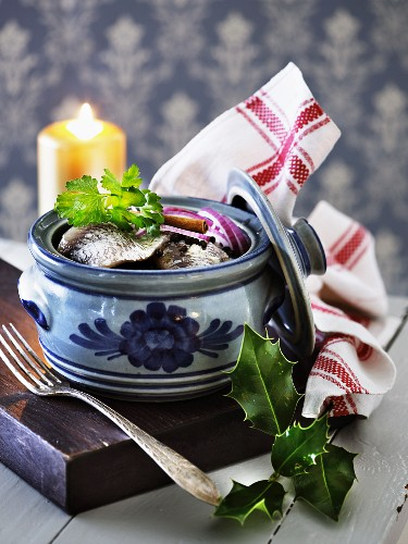 Herring fillets with onions in a ceramic pot (Scandinavia)