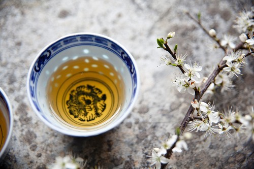 Green tea in an oriental tea bowl next to a sprig of cherry blossom
