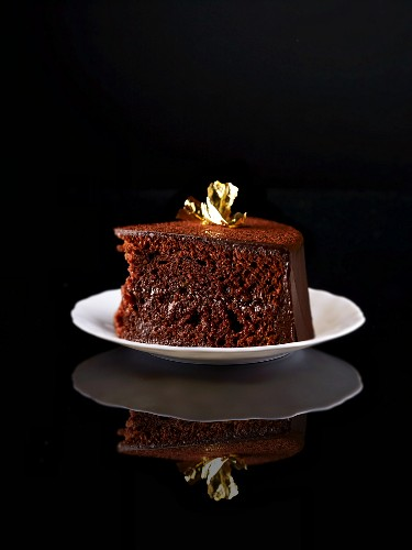 A slice of Sachertorte (rich Austrian chocolate cake) decorated with gold leaf on a plate