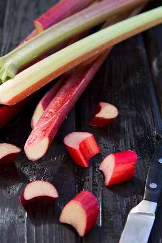 Rhubarb stalks on a wooden surface, some partially sliced