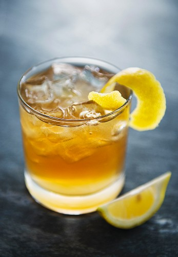 A Whiskey Sour with ice cubes garnished with lemon zest