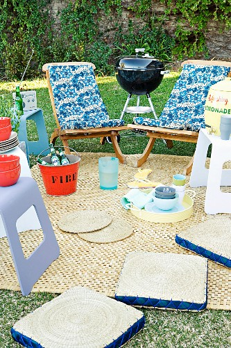 Garden picnic - various chairs and stools around blanket and mobile barbecue on lawn