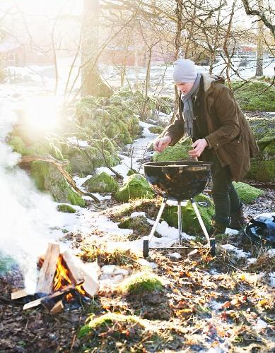 Mann grillt Pizza im winterlichen Garten