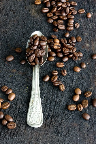 Coffee beans on an aluminium spoon