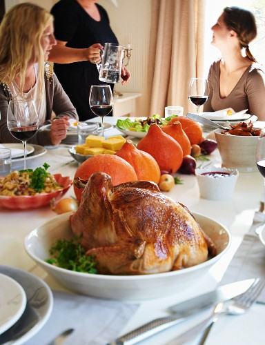 A table laid for Thanksgiving with stuffed turkey, pumpkins and cornbread