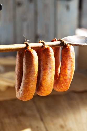 Sausages hanging on a wooden spoon