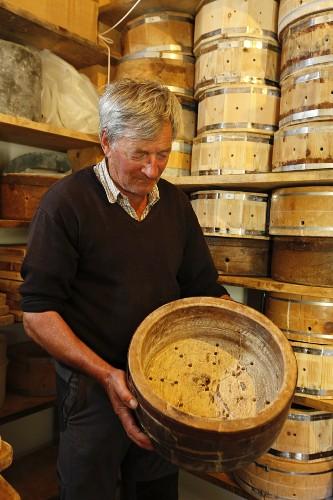 Mann mit Holzformen zur Käseherstellung