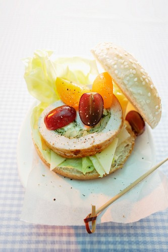 Turkey burger made with a slice of turkey roulade, grapes and yellow tomatoes