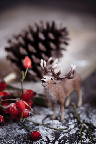 Toy stag, rose hips, pine cone and artificial snow on wooden table