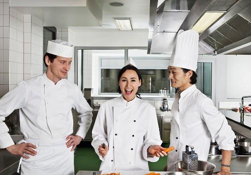 Three chefs joking around in a commercial kitchen