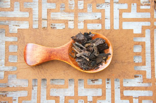 Pu-ehr tea leaves on a wooden spoon