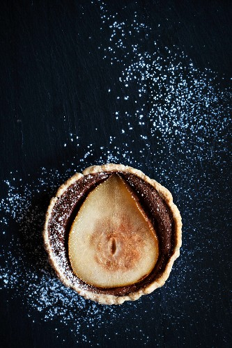 Pear and chocolate tart with icing sugar