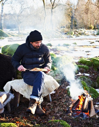 A man eating pizza by a campfire in winter