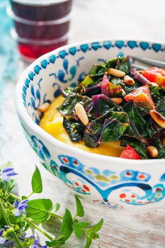 A bowl of polenta with a chard and tomato medley and pine nuts