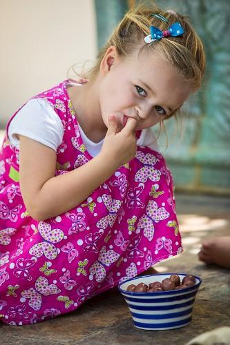 A little girl eating olives