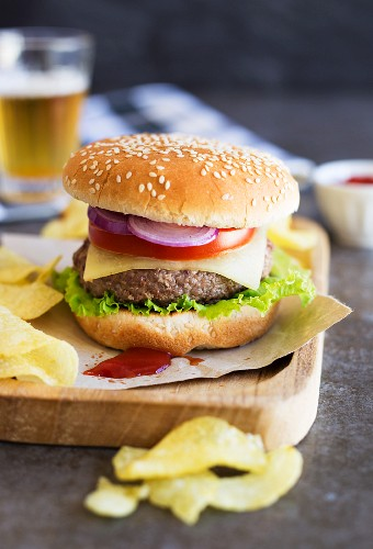 A hamburger with tomato, lettuce, onions and cheese, served with crisps and beer