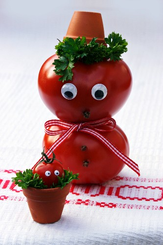 A tomato man with a face and a tomato baby in a flowerpot