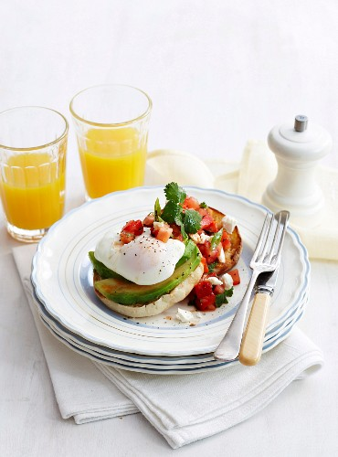 A bread roll topped with a poached egg, avocado and salsa served with orange juice (Mexico)