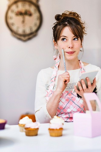 A woman in a kitchen thinking and holding a notebook and pen in her hand