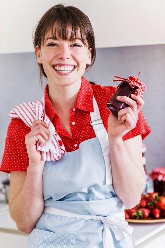 A smiling young woman holding a jar of homemade strawberry jam