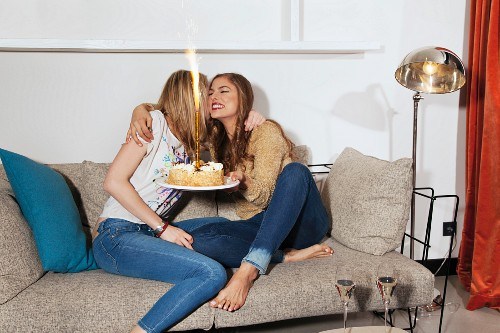 Two young women with a birthday cake hugging on a sofa