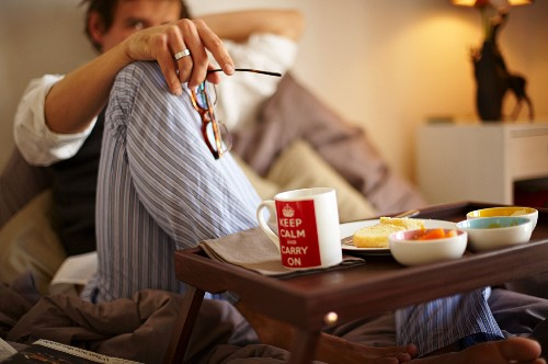 A man eating an English breakfast in bed
