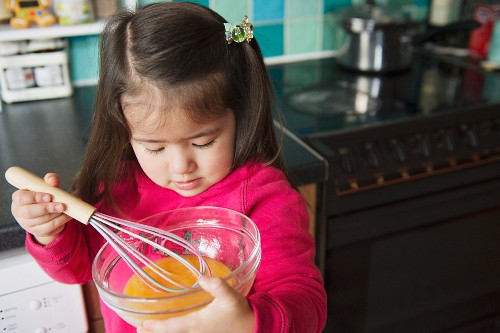 A little girl stirring egg yolk in a bowl with a whisk