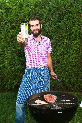 A young man wearing an apron and holding a drink standing in front of a barbecue with salmon and trout