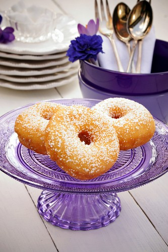 Doughnuts on a glass purple cake stand