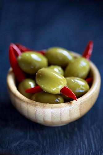 Grüne Oliven, gefüllt mit Chilischoten, im Holzschälchen