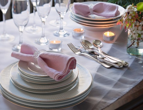 A stack of plates, cutlery and glasses on a summery table at dusk