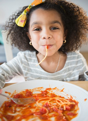 An African American girl eating spaghetti