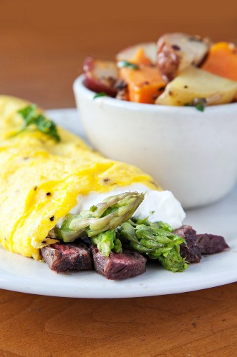 An omelette with asparagus, beef steak and a side of potatoes