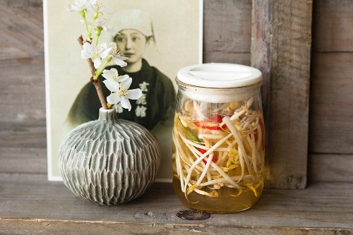 Pickled bean sprouts in jars in front of a portrait