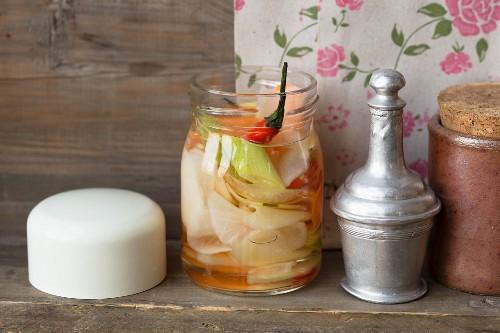 Pickled vegetables in an open screw-top jar